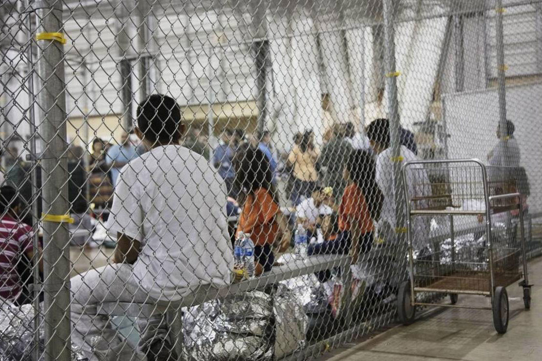 In This Photo Provided By U.S. Customs And Border Protection, People Who've Been Taken Into Custody Related To Cases Of Illegal Entry Into The United States, Sit In One Of The Cages At A Facility In McAllen, Texas (Photo By AP)