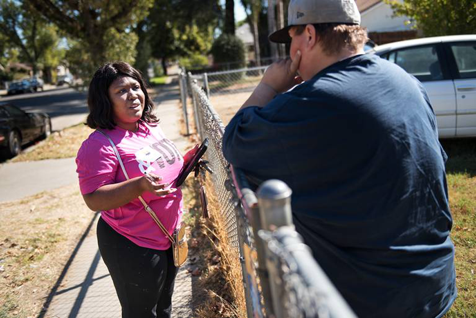 Volunteer Ambriana Williams talks with local voter Tanisha Ryder about Proposition 10 from Faith in the Valley canvas a neighborhood in Modesto, Calif., on Saturday, Oct. 13, 2018. (Andy Alfaro/Modesto Bee)